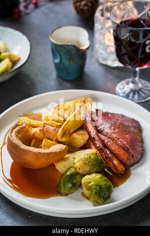 Roast dinner with beef, carrots, brussel sprouts and yorkshire pudding - Stock Photo