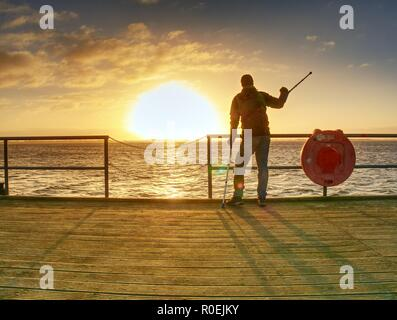 Tourist on ferry boat mole within sunrise or sunset. Warm colors, reflection of Sun in camera lens. - Stock Photo