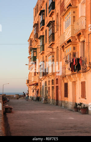 Valletta, Malta - May 2018: Real life on Valletta street during orange sunset - clothes drying on typical maltese balcony - Stock Photo