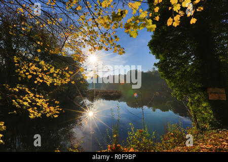 Magical colourful autumn landscape at sunrise, rising sun creating sunburst effect in the blue sky, reflected in still water of pool below. Reflection.