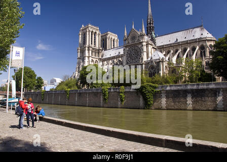 View of Notre Dame cathedral from a BatoBus (water bus) stop on the Seine river in Paris, France. - Stock Photo