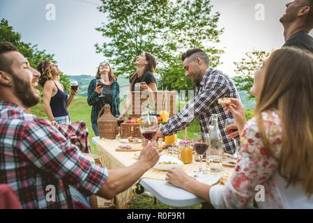 Group of friends making barbecue in the nature - Happy people having fun on a pic-nic in the countryside - Stock Photo