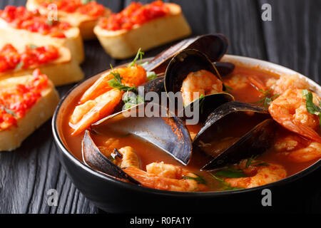 Bouillabaisse soup with seafood and fish close-up in a bowl served with toasts on the table. horizontal - Stock Photo