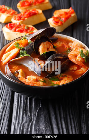 Traditional tomato seafood soup with shrimps, fish fillet and mussels closeup in a bowl on the table. vertical - Stock Photo