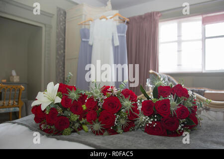 Bridal bouquets of red roses and wedding dresses hanging up in the background on a brides wedding day - Stock Photo