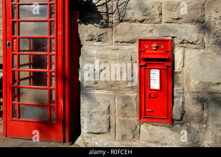 Traditional red telephone box and red Victorian post box set in wall at Bridgnorth railway station, Shropshie, England - Stock Photo