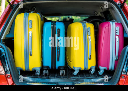 colored travel bags in car trunk - Stock Photo