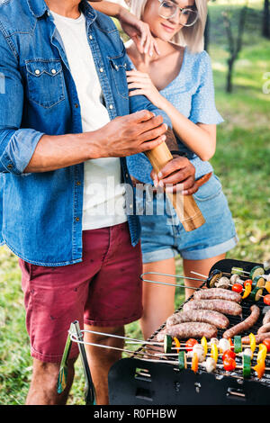 partial view of woman standing near african american boyfriend while he cooking food on grill - Stock Photo