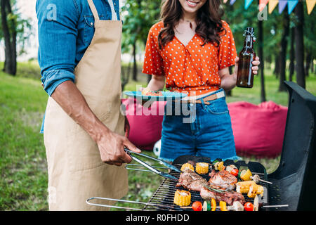 partial view of woman with beer looking at african american boyfriend cooking food on grill during barbecue - Stock Photo