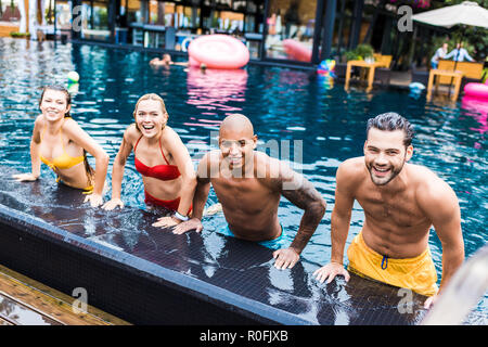 group of happy friends having fun in swimming pool - Stock Photo