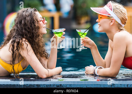 side view of two attractive smiling female friends drinking cocktails on poolside - Stock Photo
