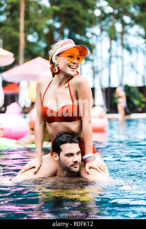 smiling woman in red swimsuit looking away while sitting on boyfriends shoulders in swimming pool - Stock Photo
