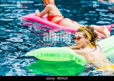 two attractive smiling women in swimsuits resting on inflatable mattresses in pool - Stock Photo