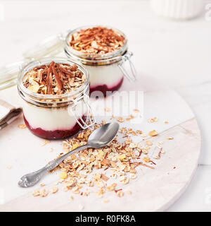 Healthy breakfast. Two jars of healthy yogurt with strawberry sauce, oat and chocolate on white marble serving plate. Square crop. - Stock Photo