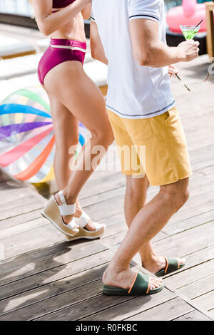 cropped image of couple standing with cocktail near swimming pool - Stock Photo
