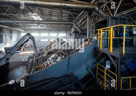 Refiner and chain-stepped conveyor equipment of modern waste recycling plant transports waste from receiving department loaded by manipulator to sorti - Stock Photo