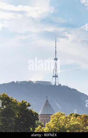 View of TV tower on Mtatsminda Mountain and church in Tbilisi, Georgia. Trees foreground. - Stock Photo