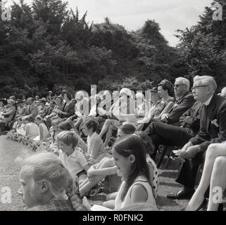 1967, picture shows a large group of spectators watching an event at the Tring Arts summer festival, Tring, Hertfordshire, England, UK. The festival was outdoors at Tring Park, the school for the Performing Arts, the home of the Arts Educational School. - Stock Photo