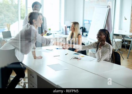 Negotiating business, awesome mixed race girls shaking hands after successful contract - Stock Photo