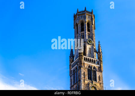 The Belfry (Belford) Tower against blue sky in the center of the historic city of Bruges, Belgium - Stock Photo