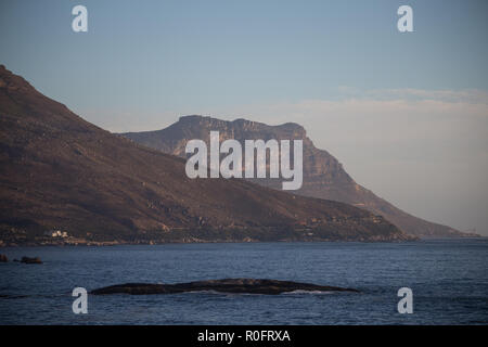 scenic view over Atlantic Ocean and Oudekraal with Victoria Rd coastal drive running beneath Twelve Apostle Mountain range Cape Town South Africa - Stock Photo