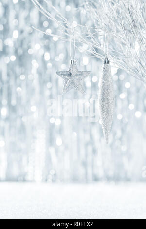 Shiny silver christmas ornaments hanging on a tree, with defocused christmas lights in the background. - Stock Photo
