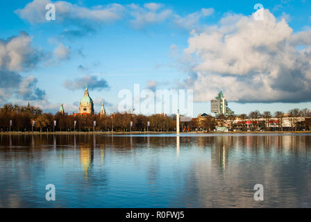 A panorama showing the town hall, a skyscraper, a cloudy blue sky and the lake Maschsee in Hanover, Germany - Stock Photo
