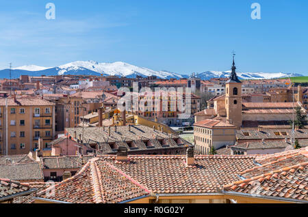 View over the rooftops of the old town towards snow-capped mountains, Segovia, Castilla y Leon, Spain - Stock Photo