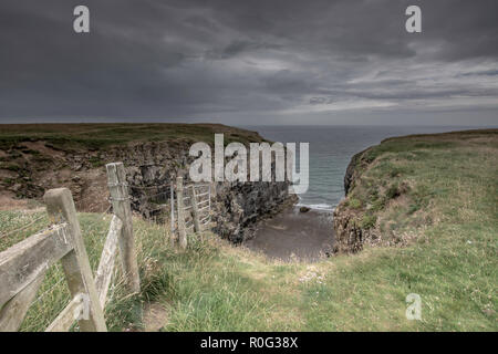 Wooden fence on cliff edge and old limestone quarry on Pembrokeshire coast, South Wales,UK.View from cliff top, coastal path.Dramatic sky with dark ra - Stock Photo