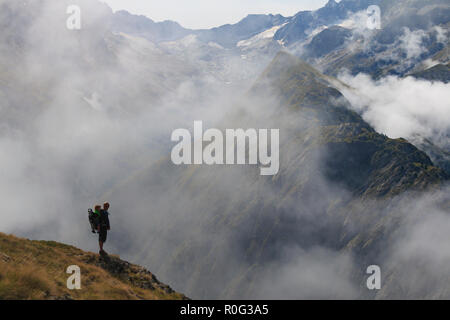 Hiker in France alps standing on edge of mountain with baby on his back. - Stock Photo