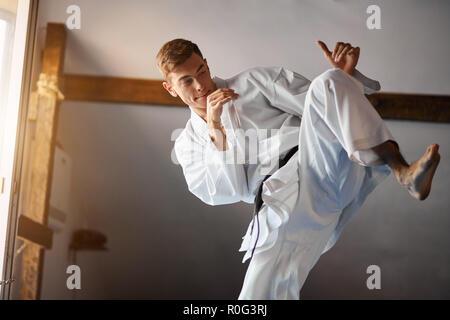 black belt karate fighter training hight kick - Stock Photo