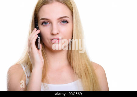 Close up of young beautiful teenage girl talking on mobile phone - Stock Photo