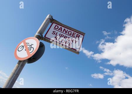 DANGER Slippery Slope sign - Stock Photo