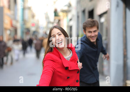 Happy couple running together towards camera in the street in winter - Stock Photo