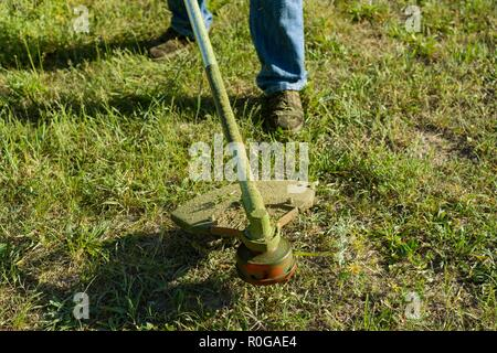Man mowing grass on a rural lawn, close-up, - Stock Photo