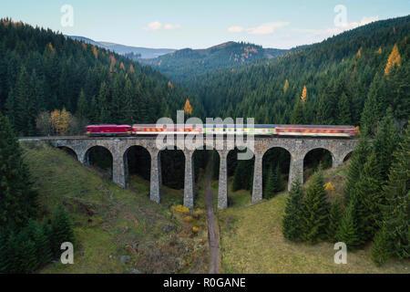 Train passing through Chmarossky viaduct close to village Telgart, Slovakia - Stock Photo