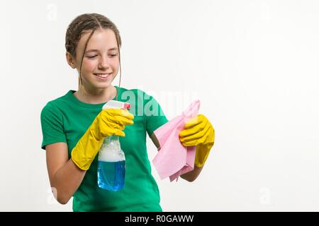 Cleaning day, spring cleanup, housework concept. Girl teenager in yellow gloves with rag and spray detergent. White background, copy space - Stock Photo