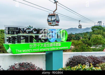 Hong Kong - January 26, 2016: Ngong Ping 360 Skyrail on Lantau Island in Hong Kong is the worlds most amazing cable car experience. Big sign on cablew - Stock Photo