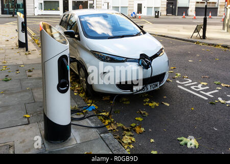 White Renault Zoe Dynamique NAV electric car charging at kerbside charging point. - Stock Photo