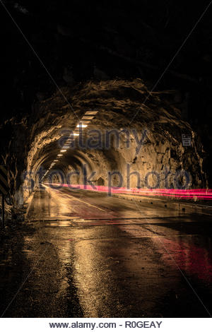 Tunnel in Yosemite National Park at night. Car driving through long exposure with red light trails from tail lights. Dark and mysterious - Stock Photo