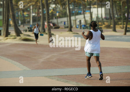 Durban, KwaZulu-Natal, South Africa, single adult male in running sportswear with muscular body taking early morning run on beachfront promenade - Stock Photo