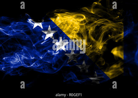 National flag of Bosnia and Herzegovina made from colored smoke isolated on black background. Abstract silky wave background - Stock Photo