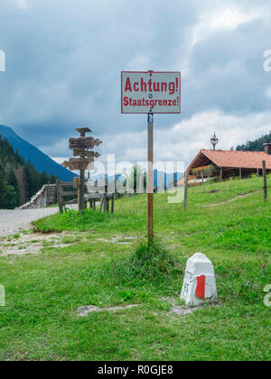 Schwangau, Germany - July 11, 2018: Border sign and landmark between Germany and Austria on the Salober-Alm photographed from Germany. - Stock Photo