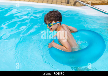 side view of happy boy in swimming glasses with inflatable ring swimming in swimming pool on summer day - Stock Photo
