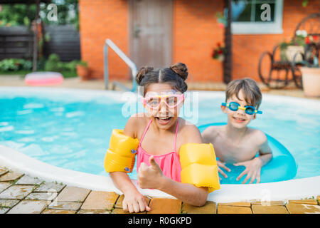 little siblings swimming in swimming pool together on summer day - Stock Photo