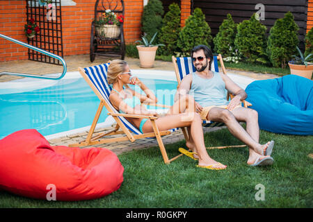 smiling couple on beach chairs spending time near swimming pool on backyard on summer day - Stock Photo