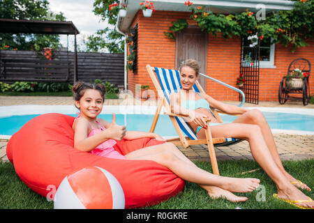 mother and smiling daughter resting near swimming pool on backyard on summer day - Stock Photo