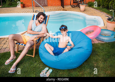 smiling father and son resting near swimming pool on backyard on summer day - Stock Photo
