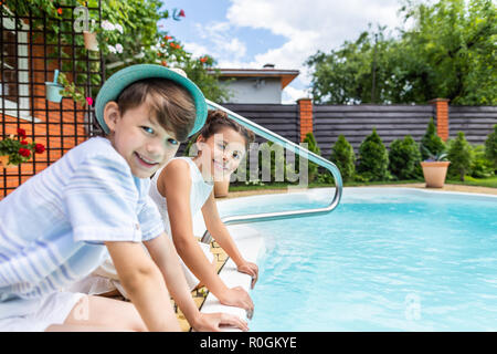 side view of little siblings sitting near swimming pool on summer day - Stock Photo