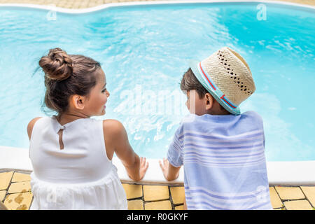 back view of little siblings sitting near swimming pool on summer day - Stock Photo